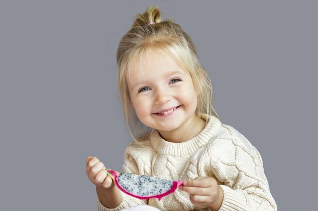Menina loura pequena bonito que come a fruta fresca do dragão isolada no cinza