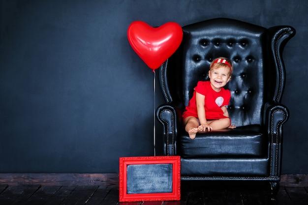 Menina loura pequena no vestido vermelho com a grinalda vermelha com os corações que sentam-se na poltrona com o balão vermelho do coração no dia do valentim do st.