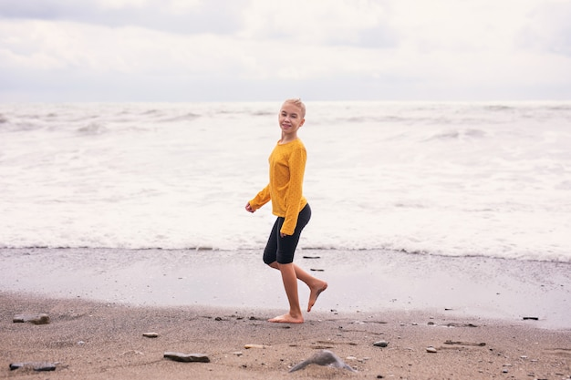 Menina loura que corre e que salta na praia na costa de mar azul em férias de verão no tempo do dia.