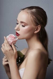 Menina loura que guarda flores cor-de-rosa perto da cara. beleza