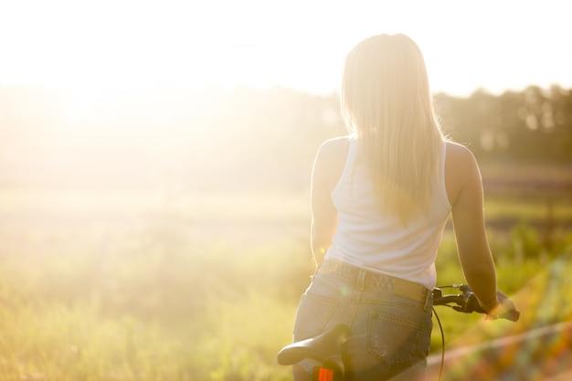 Menina loura volta andar de bicicleta