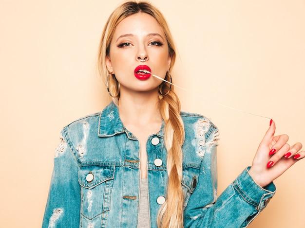 Menina má hipster jovem bonita em roupas da moda jeans e brinco no nariz. modelo positivo se divertindo.ela puxando uma goma de mascar