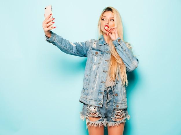Menina má hipster jovem bonita em roupas da moda jeans verão e brinco no nariz. modelo positivo lambendo doces de açúcar redondos. toma selfie foto