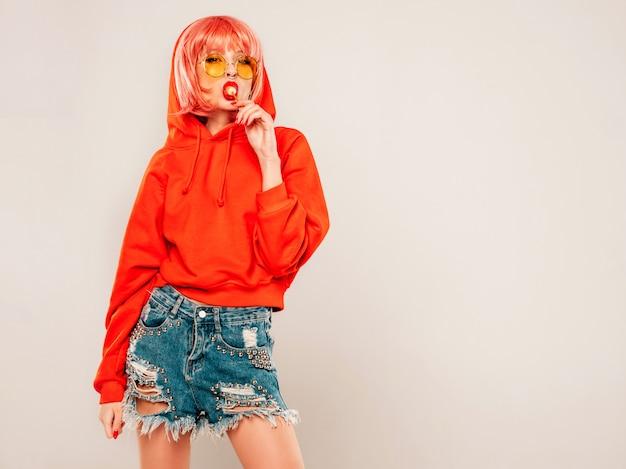 Menina má hipster jovem bonita no capuz vermelho na moda verão vermelho e brinco no nariz. mulher despreocupada sexy posando no estúdio em fundo cinza na peruca. modelo quente lambendo doces de açúcar redondos