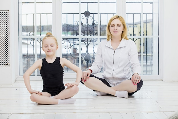 Menina mãe e filha fazendo ioga feliz e belas casas no chão de madeira na janela