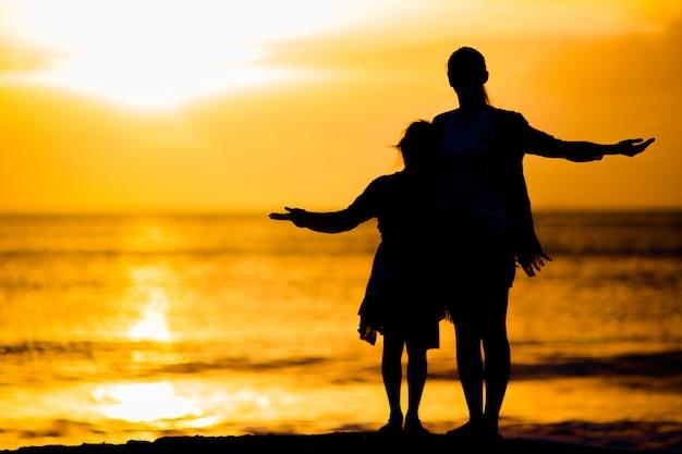 Menina, mãe feliz silhueta por do sol na praia