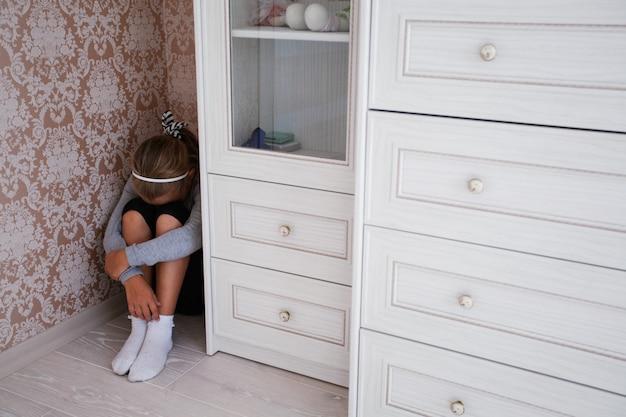 Menina magoada, sentada no canto do quarto