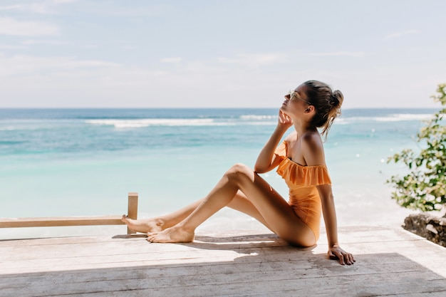 Menina magra pensativa, sentada no chão com os olhos fechados e ouvindo as ondas do mar. foto ao ar livre de uma linda mulher europeia posando na costa do mar.