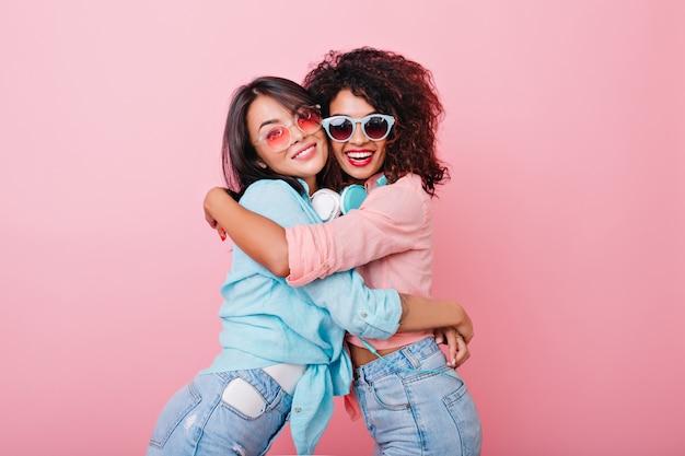 Menina magro animada com penteado africano, abraçando a amiga asiática em óculos de sol coloridos da moda. senhora muito europeia em jeans abraços jovem negra em camisa rosa.