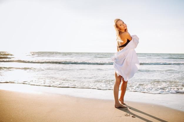 Menina magro de luxo em um biquíni preto e camisa branca na praia oceano