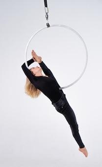 Menina magro e flexível em um aro aéreo isolado em um fundo branco.
