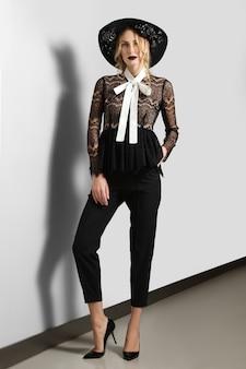 Menina magro em calças curtas, blusa de renda transparente e chapéu posando perto da parede