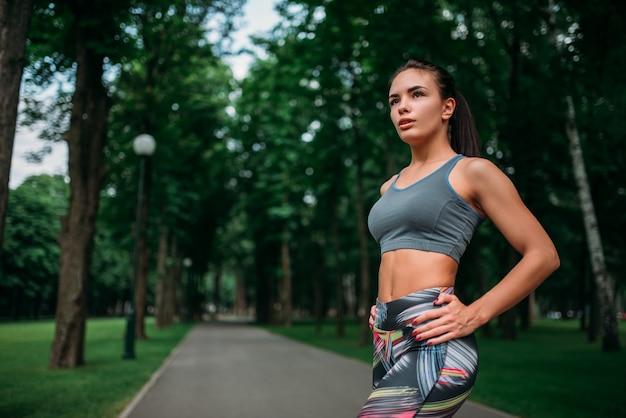 Menina magro em roupas esportivas, treinamento de fitness ao ar livre. mulher atlética fazendo exercícios no parque de verão