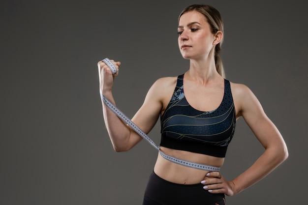 Menina magro em um top de esportes com uma fita de centímetro na cintura em uma parede preta