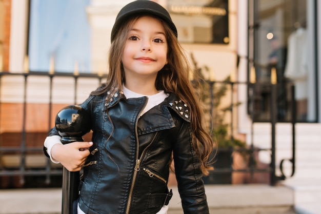 Menina magro interessada com longos cabelos escuros posando em frente ao prédio da escola ao lado do pilar de ferro.