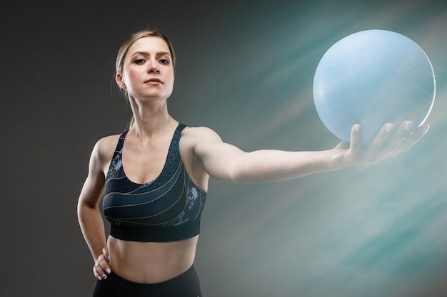 Menina magro no sportswear segura uma bola de esportes em uma parede preta com efeito de reflexo de lente