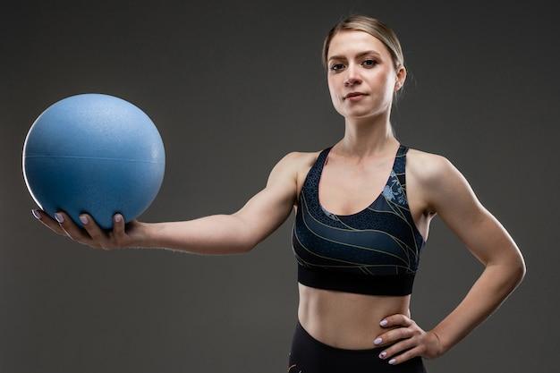 Menina magro no sportswear segura uma bola de esportes em uma parede preta