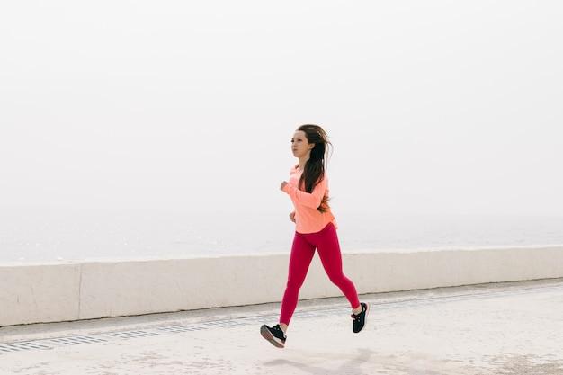 Menina magro no sportswear vermelho correndo na praia de manhã