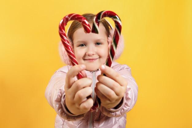 Menina mantém doces de natal em forma de um coração.