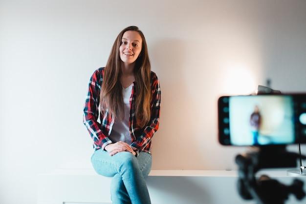 Menina mantém seu blog no telefone enquanto está sentado em casa contra uma parede branca.