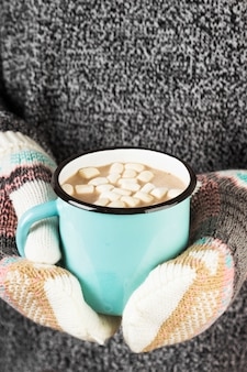 Menina mantém uma caneca de chocolate quente com marshmallows em luvas