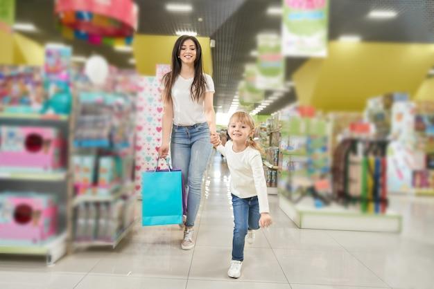 Menina, mantendo a mão da mãe e correndo para a frente na loja