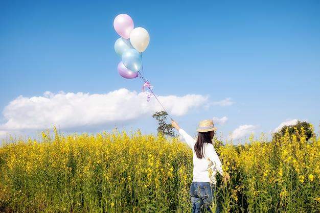 Menina mão segurando balões multicolor