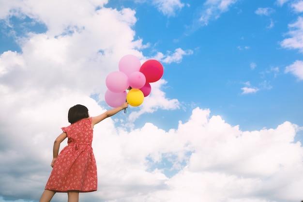Menina, mão, segurando, multicolorido, balões, feito, conceito, de, feliz aniversário, em, verão