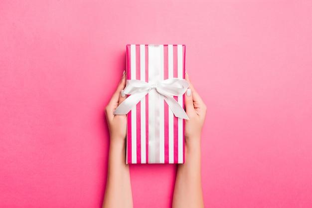 Menina mãos segurando uma caixa de presente de papel ofício rosa