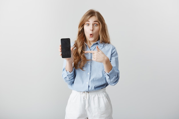 Menina maravilhada com o novo telefone. retrato de jovem europeu chocado e fascinado com cabelo loiro na blusa mostrando smartphone, apontando para o dispositivo, dizendo uau, expressando espanto