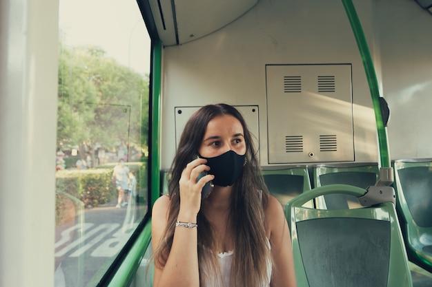 Menina mascarada falando ao telefone no ônibus municipal