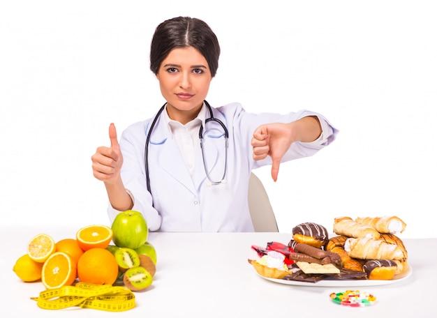 Menina médico é a escolha entre alimentos saudáveis e insalubres.