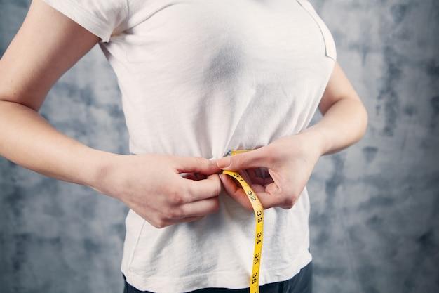 Menina medindo a barriga com um centímetro