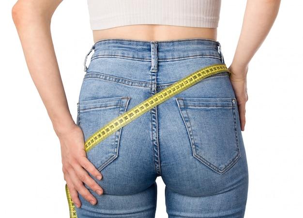 Menina medindo suas nádegas e quadris