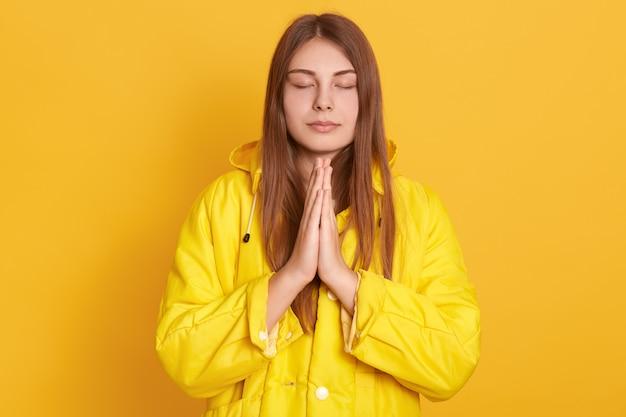 Menina meditando ou rezando na parede amarela