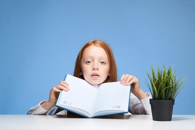 Menina menina criança fazendo lição de casa, sentado em uma mesa