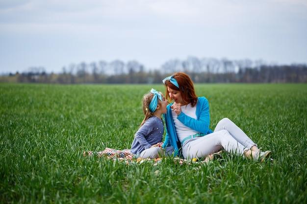 Menina menina e mãe mulher sentada na colcha e comendo biscoitos e geleia, grama verde no campo, clima ensolarado de primavera, sorriso e alegria da criança, céu azul com nuvens