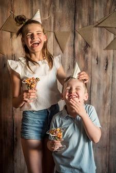 Menina, menino, compartilhando comendo pipoca na festa de aniversário