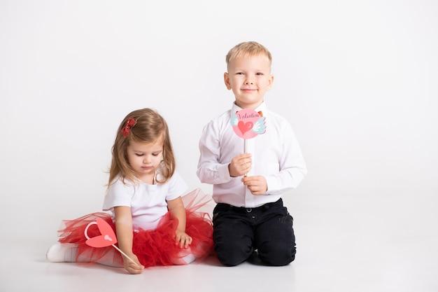 Menina menino e criança detém os chapéus de coco ou stikcers com desenho de dia dos namorados na parede branca.