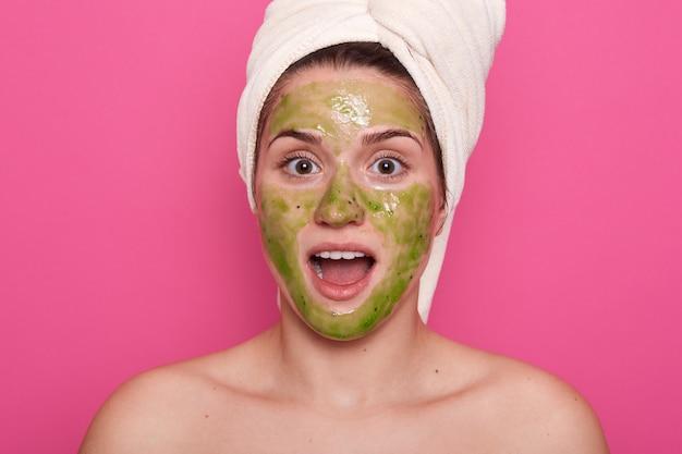 Menina mesquinha com máscara facial de argila verde. foto de menina surpresa com uma toalha branca na cabeça dela