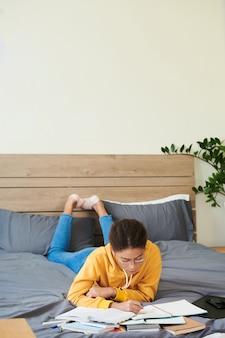 Menina mestiça concentrada de óculos deitada na cama e lendo anotações em apostilas enquanto se prepara para o exame