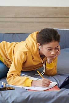 Menina mestiça do ensino médio descontente com fones de ouvido sem fio, deitada na cama e fazendo anotações enquanto resolvia tarefas escolares