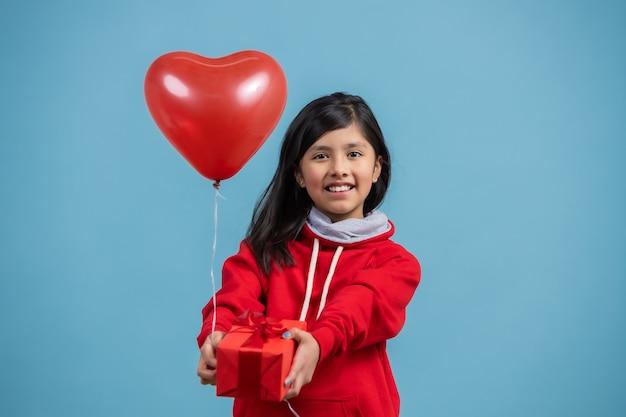Menina mexicana entregando um presente vermelho e um balão de coração, dia das mães