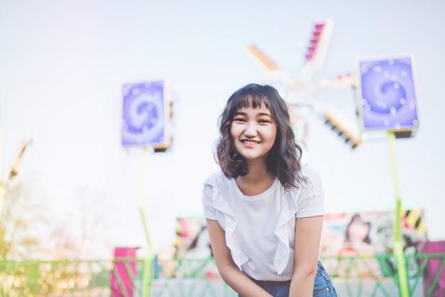 Menina milenar asiática nova bonita em um parque de diversões, sorrindo. copie o espaço.