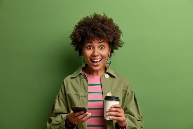 Menina milenar de pele escura radiante, feliz por receber uma mensagem inesperada no smartphone, segurando um copo de papel com um café cheio de energia, vestida com roupa da moda, posa sobre a parede verde.