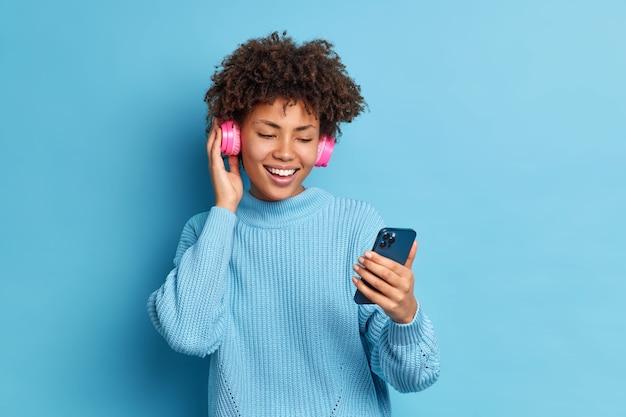 Menina milenar positiva entretida com cabelo encaracolado segurando smartphone faz videochamada e usa fones de ouvido estéreo para ouvir suas músicas favoritas vestida com um macacão quente