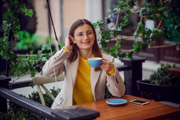 Menina milenar sentada na esplanada de um café a tomar café