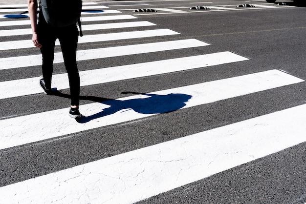 Menina millenial nova que cruza uma passagem pedestre no meio-dia.