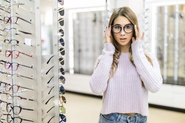 Menina minúscula com longos cabelos dourados e aparência de modelo demonstra a diferença dos óculos em loja profissional