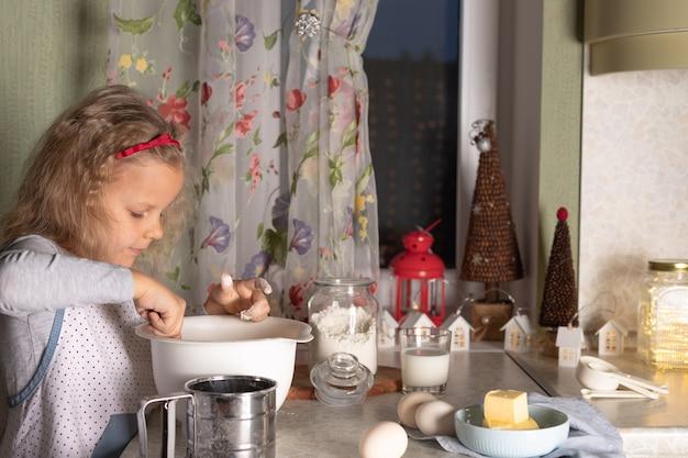 Menina misture ingredientes para massa em uma tigela com decorações de natal